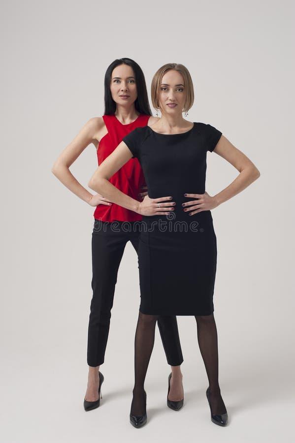 Två säkra affärskvinnor som står med händer på höfterna royaltyfria foton