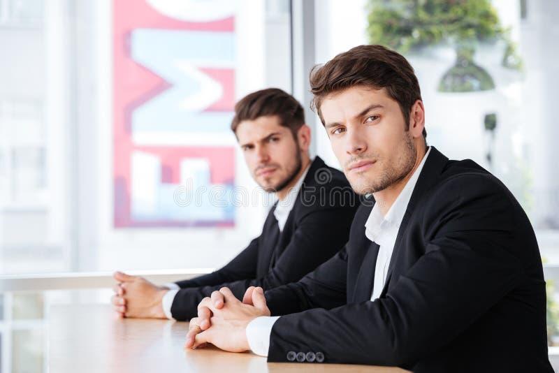 Två säkra affärsmän i dräkten som i regeringsställning sitter tillsammans royaltyfri foto