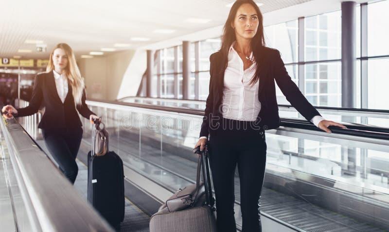 Två säkra kvinnor som bär formella dräkter som står på rullbandstrottoaren i flygplats royaltyfri fotografi