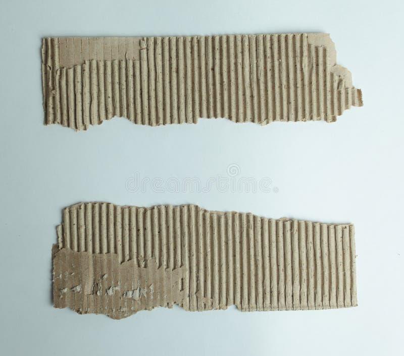 Två sönderrivna stycke av papp på vit bakgrund royaltyfri foto