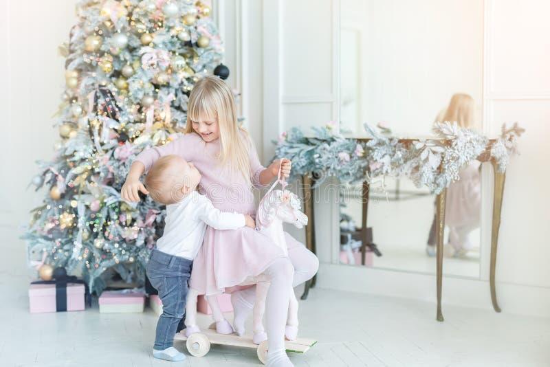 Två söta små syskon och syskon som har kul med att leka med baktrullösa hästar nära julträd i royaltyfri bild