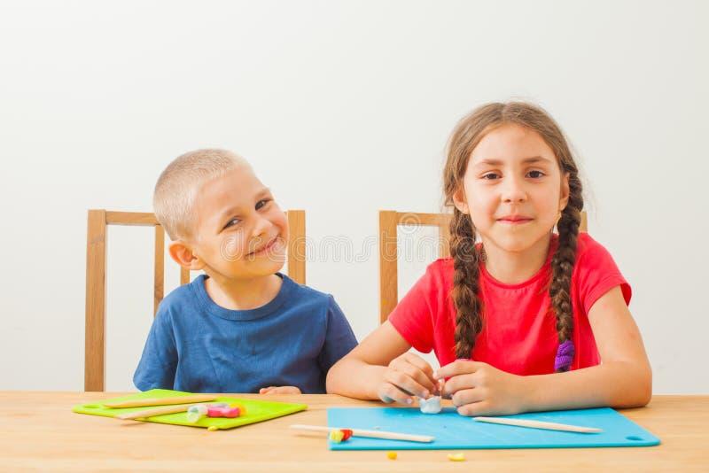 Två söta små syskon som har kul tillsammans med färgstark modellering arkivfoto
