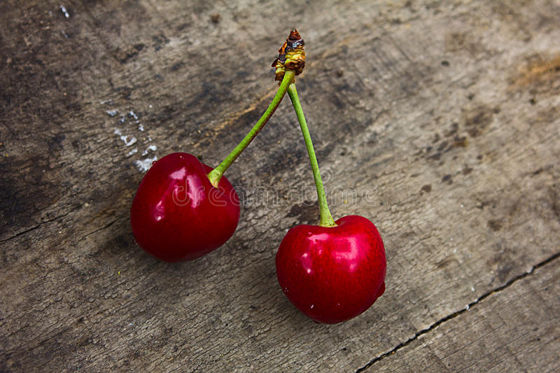 Två saftiga körsbär av ljus röd färg på en brun bakgrund av trä arkivfoton