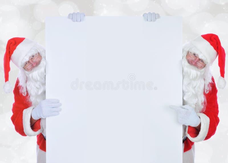 Två Santa Claus på antingen sida av ett stort tomt tecken arkivbilder