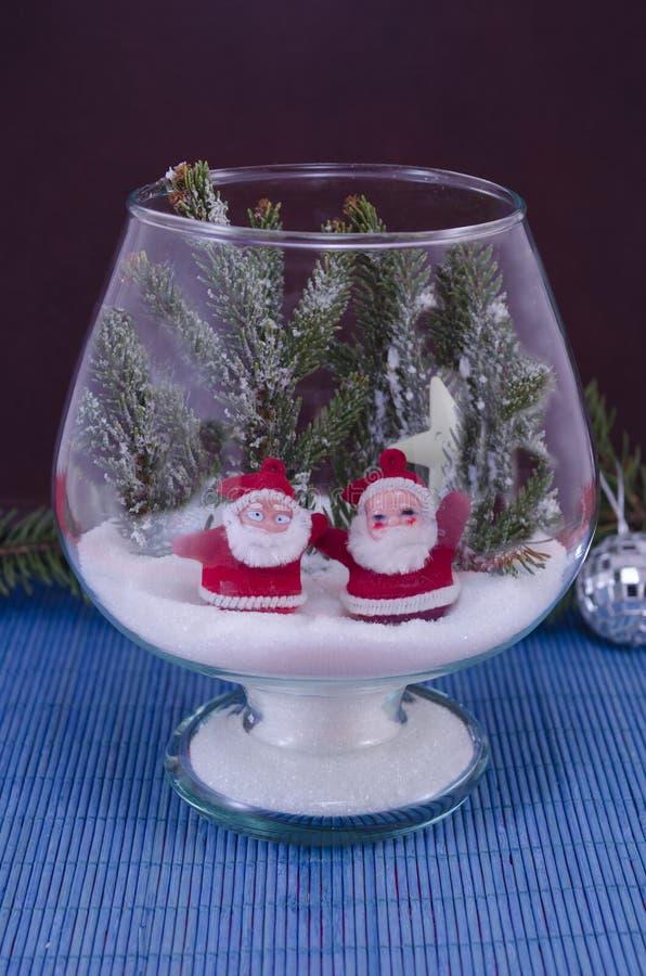 Två Santas i en glass bunke som täckas med snö arkivfoton