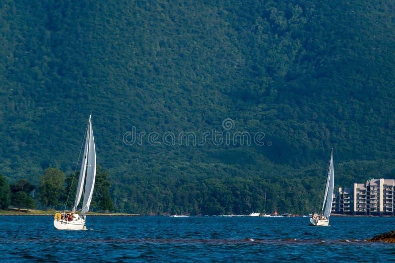 Två seglar fartyg på sjön vid berget fotografering för bildbyråer