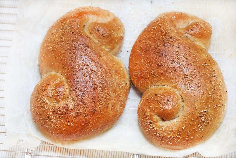 Två sesambrödrullar på bakningpapper, matlagning royaltyfri bild