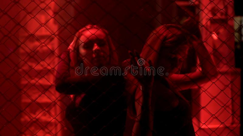 Två sexiga damer som står bak metallkedja, fäktar i rött ljus, uteliv royaltyfri foto