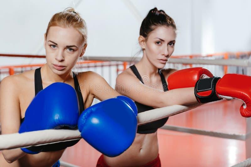Två sexiga idrotts- flickor som lutar på repen royaltyfria foton