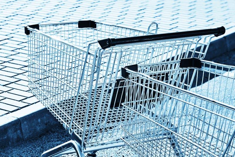 Två shoppingvagnar i en lagerparkeringsplats Blå toning fotografering för bildbyråer