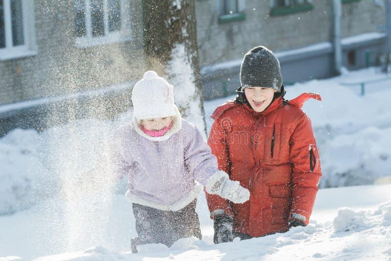 Två siblingbarn som utomhus spelar, genom att kasta snökorn i solig dag för frostig vinter royaltyfri bild
