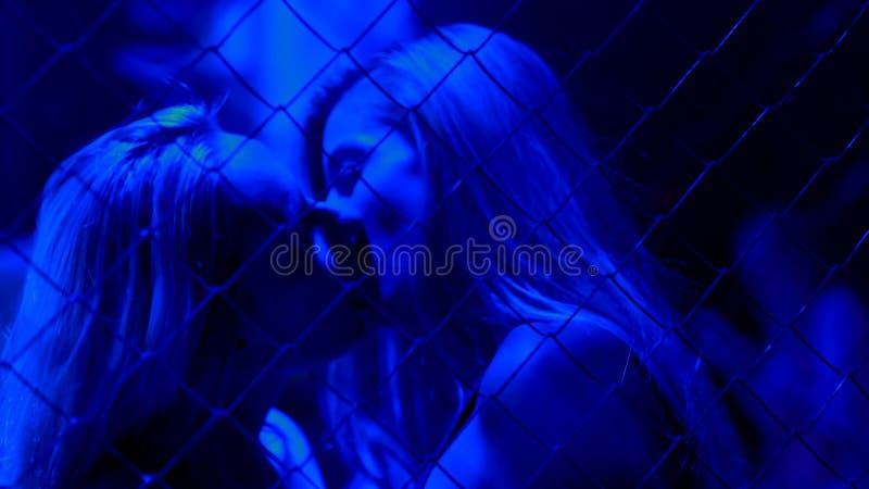 Två sinnliga kvinnor som passionately kysser bak metallkedjestaketet, en nattställning royaltyfri fotografi