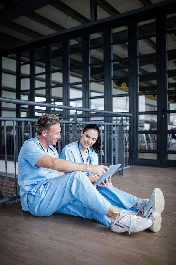 Två sjuksköterskor som sitter på golv och samtal royaltyfri foto