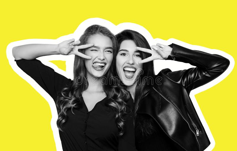 Två skämtsamma flickor som gör en gest v-tecknet nära ögon på guling arkivbilder