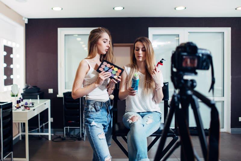 Två skönhetbloggers som gör smink- och haircareprodukter, granskar att filma det på kameran för deras vlog arkivbild