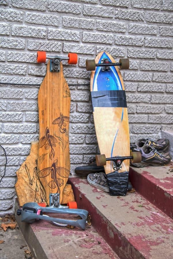Två skateboarder - en som repareras med kanalbandet - propped mot en vägg på smutsiga grungy konkreta moment med gamla kastade te royaltyfria bilder