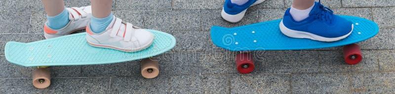Två skateboarder för barn` s, slut-UPS, med stående fot på dem arkivbilder