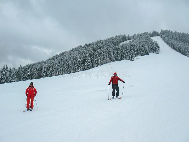Två skidåkare, en man och en kvinna, i röd kläder på a skidar spåret i bergssida royaltyfria bilder
