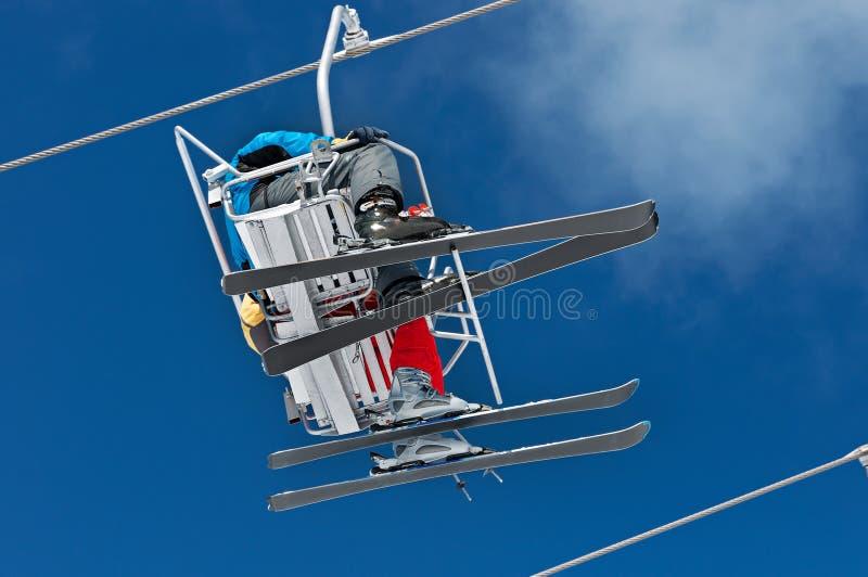 Två skidåkare lyfter till den Ski Resort höjdpunkten i vintersnöbergen på stolkabelbilen arkivbild