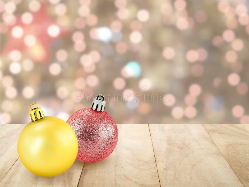 Två skinande jul klumpa ihop sig gul guld och rött på överkant för tappningbruntträtabell med defocused liten färgrik ljusbok fotografering för bildbyråer