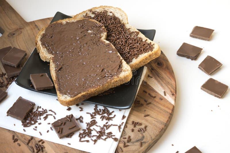 Två skivor av bröd på träplattan med chokladpasta och hagel, holländsk hagelslag arkivbild