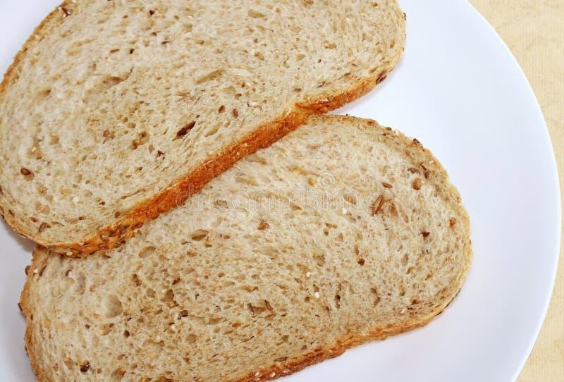 Två skivor av helt kornbröd på en vit platta arkivbilder