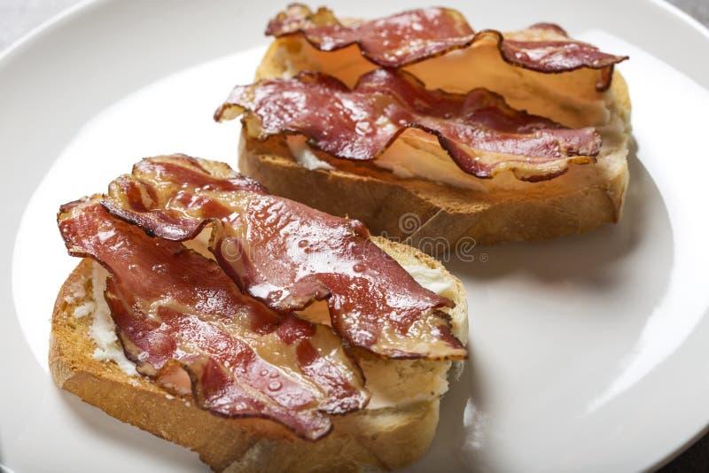 Två skivor av stekt bröd med smör och stekt bacon royaltyfri fotografi
