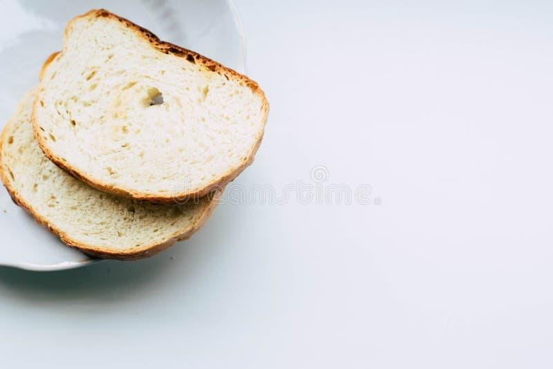 Två skivor av vitt bröd på en platta arkivfoto