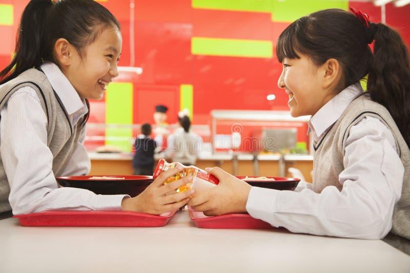 Två skolaflickor talar över lunch i skolakafeteria royaltyfri foto