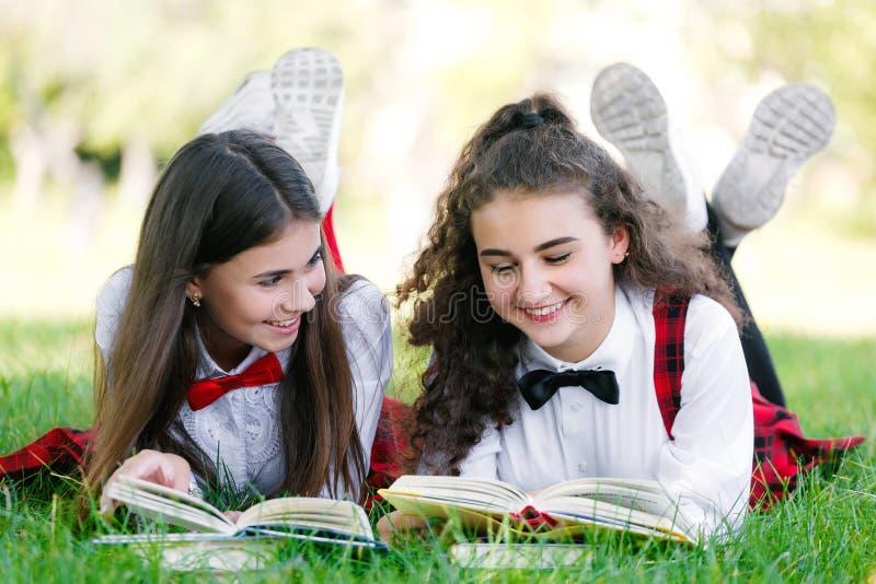 Två skolflickor i röda skolalikformig ligger på en grön gräsmatta med böcker royaltyfri foto