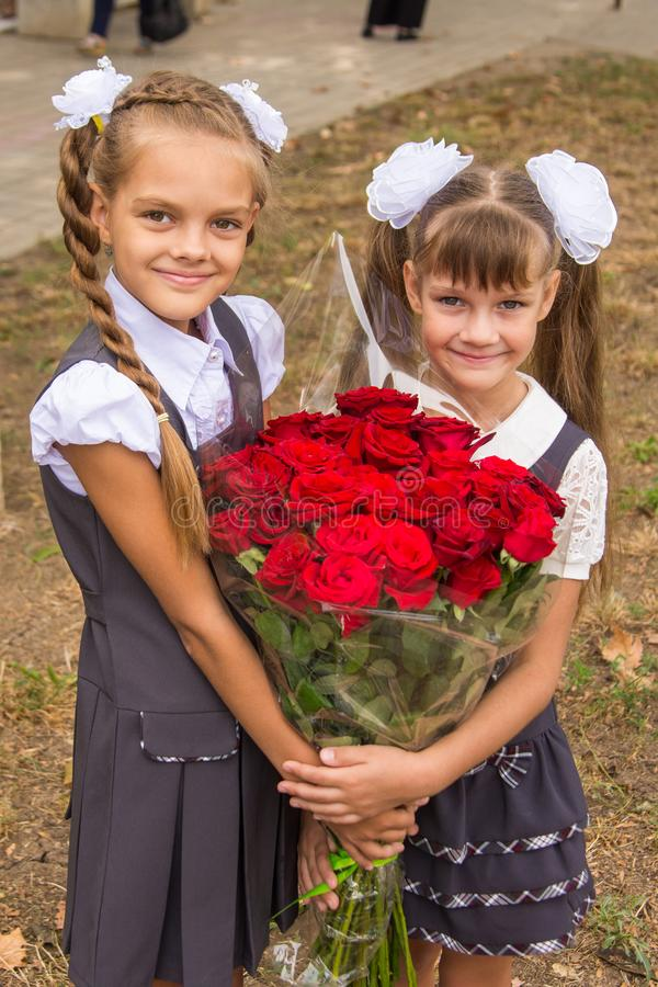 Två skolflickor rymmer en stor bukett av blommor i deras händer arkivbild