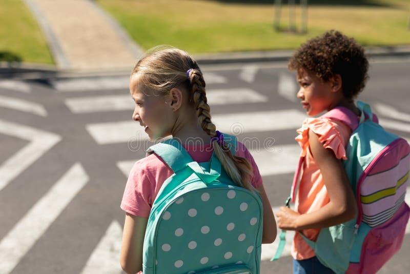 Två skolflickor som letar efter trafik medan de väntar på att ta sig över vägen arkivbild