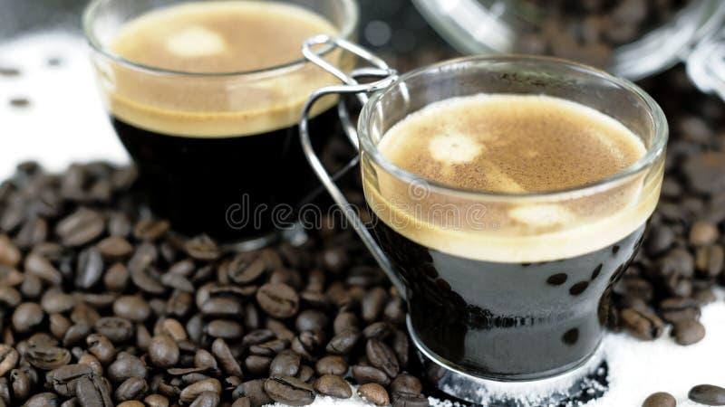 Två skott av espressosammanträde i en säng av kaffebönor arkivfoton