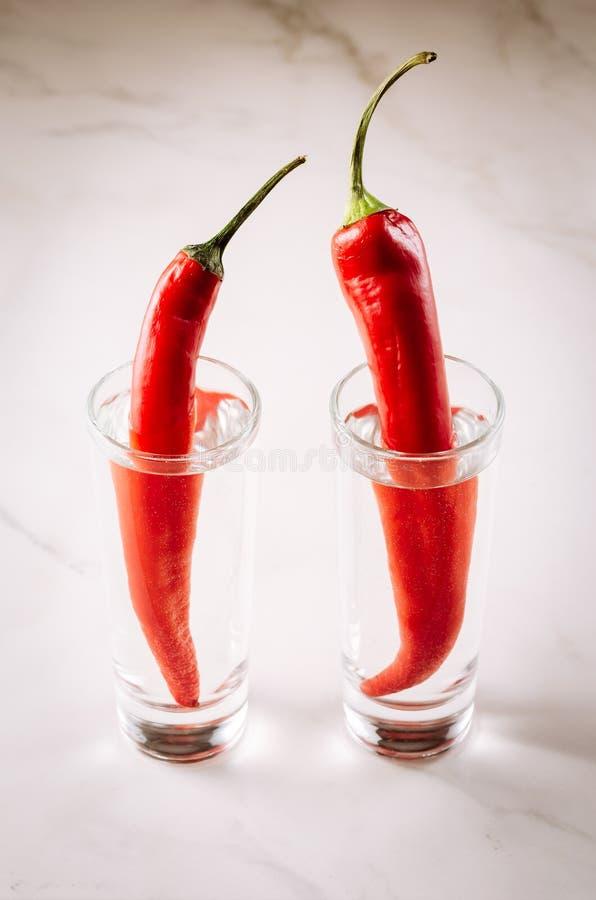 två skott av skott för vodka och för röd chili för peppar/rwoav vodka och peppar för röd chili på en vitmarmorbakgrund Selektivt  royaltyfri fotografi