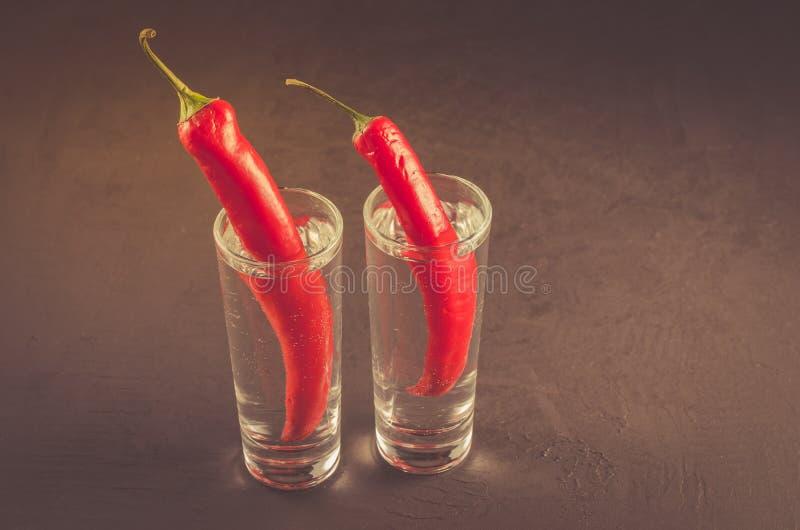 Två skott av vodka och röd peppar/två skott av vodka och röd peppar på en mörk bakgrund Selektiv fokus och copyspace arkivfoton
