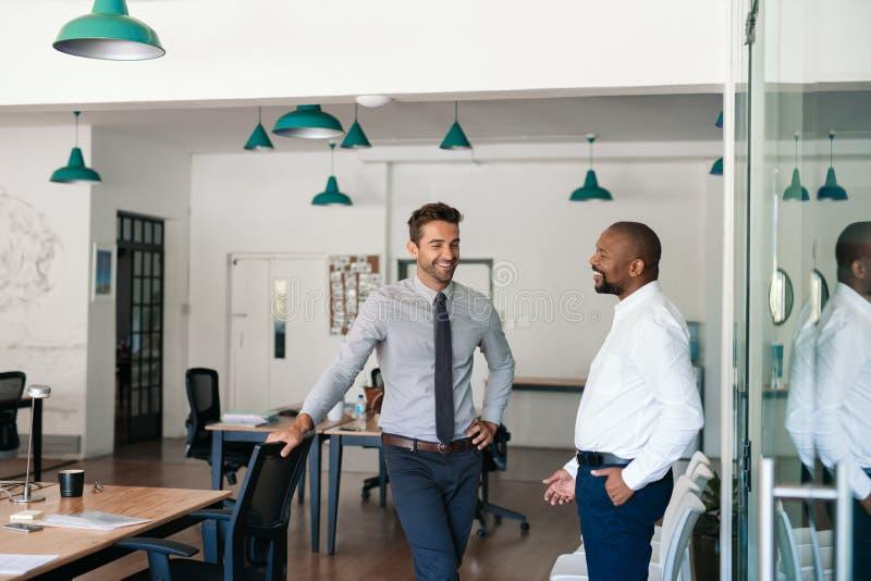 Tv? skratta aff?rsm?n som tillsammans talar i ett kontor royaltyfri bild