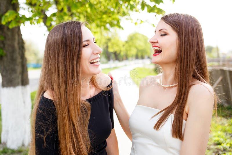 Två skratta damer i den stående klänningen utomhus royaltyfri fotografi
