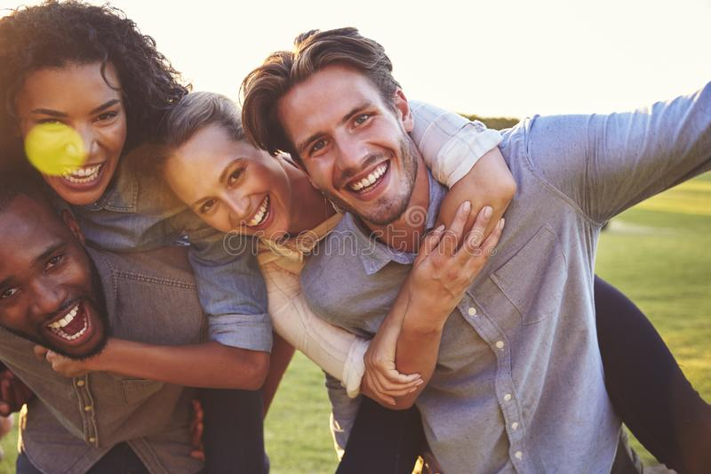 Två skratta par som utomhus piggybacking, tätt upp royaltyfri fotografi