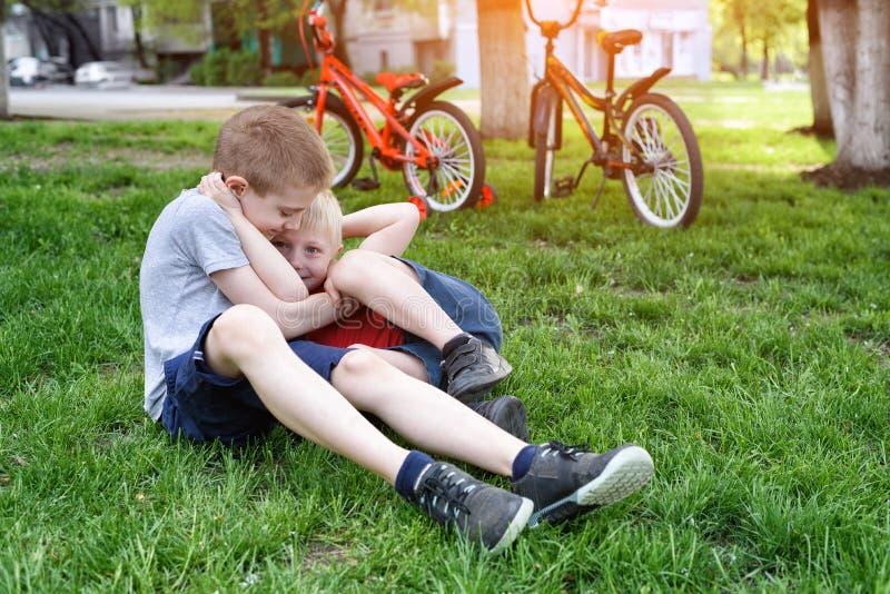 Två skratta pojkar som har gyckel på gräset Cyklar i bakgrunden arkivbilder