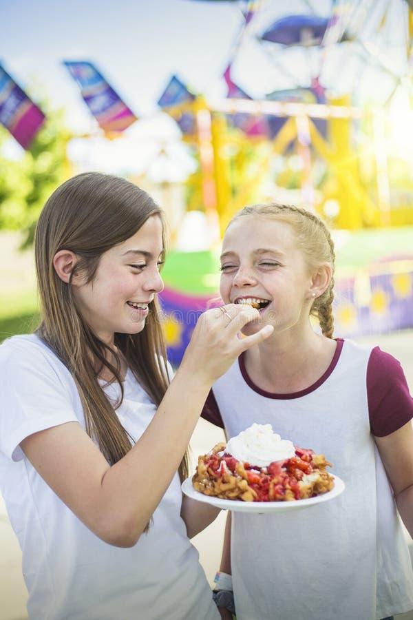 Två skratta tonårs- flickor som äter en tratt, bakar ihop och piskade kräm royaltyfria bilder