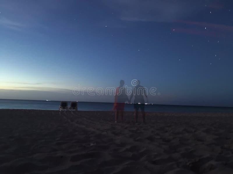 Två skuggor av vänner på en solnedgångstrand arkivbild