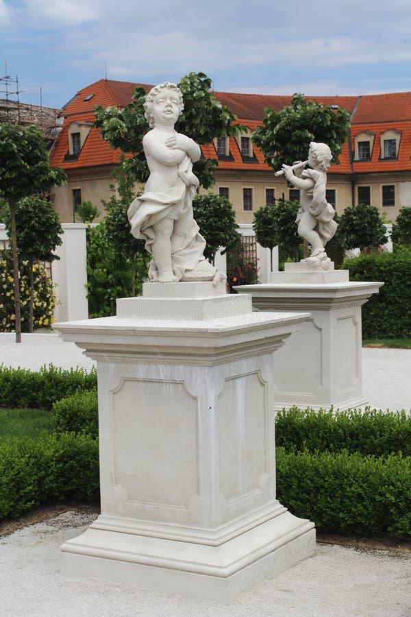 Två skulpturer av änglar på en härlig barock arbeta i trädgården arkivfoton