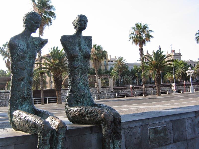 Två skulpturer av en man och kvinnor utan armar satt längs en gata av Barcelona i Spanien royaltyfria foton