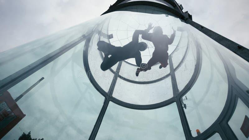 Två skydivers flyger in i vindtunnelen Extrem hoppa med fritt fall tandemcykel i vindtunnel arkivbild