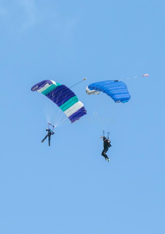 Två skydivers som utför att hoppa med fritt fall med, hoppa fallskärm arkivfoton