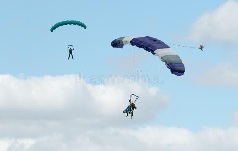 Två skydivers som utför att hoppa med fritt fall med, hoppa fallskärm royaltyfri fotografi