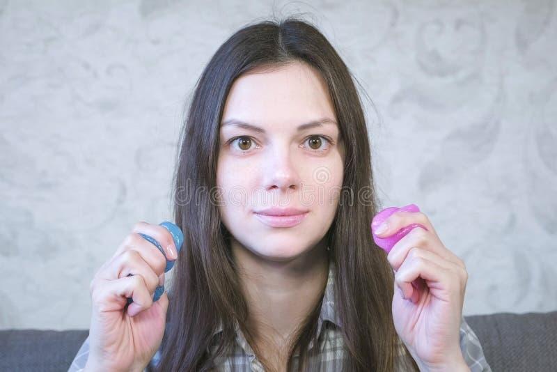 Två slammar som är rosa och som är blåa i kvinnas händer Spela med slam royaltyfri foto