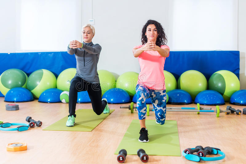 Två slanka Caucasian kvinnor som övar på mats som gör utfall med armar ut som är främsta av dem i konditionklubba royaltyfri fotografi
