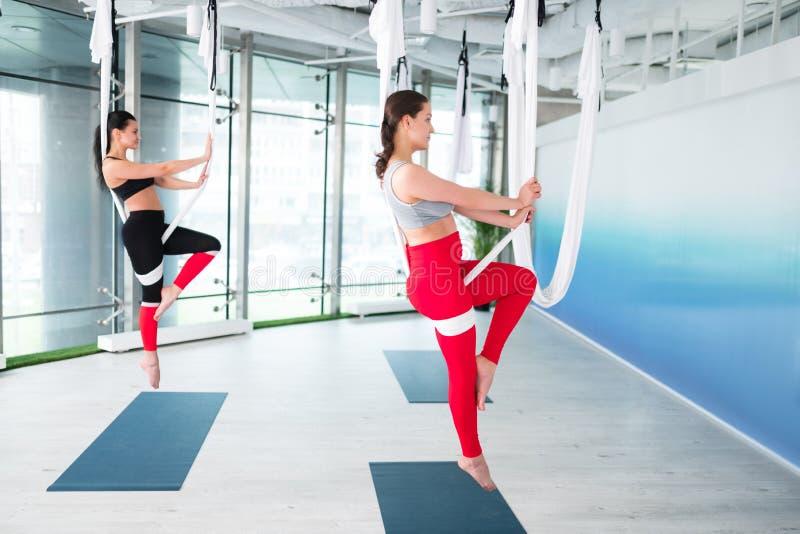 Två slanka kvinnor som bär damasker, och överkant som gör antigravity yoga arkivbilder