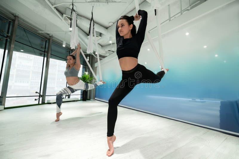 Två slanka kvinnor som bär damasker och blast som gör flyg- yoga fotografering för bildbyråer